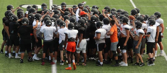 Central Kitsap head coach Mark Keel (center orange hat) raises his fist in the air as the team breaks their huddle after warm-ups during practice at the Kitsap Credit Union Athletic Complex in Silverdale on Tuesday, September 3, 2019.