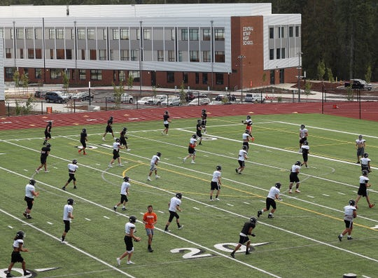 Central Kitsap High School looms in the background as the Cougars warm up on the turf field during practice at the Kitsap Credit Union Athletic Complex in Silverdale on Tuesday, September 3, 2019.