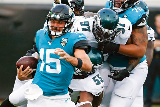 Eagles defensive tackle Malik Jackson (97) and defensive end Brandon Graham (55) chase down Jaguars quarterback Gardner Minshew (15) during the first half of an NFL preseason football game, Thursday, Aug. 15, 2019, in Jacksonville, Fla. (AP Photo/Stephen B. Morton)
