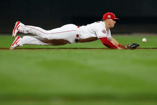 Cincinnati Reds third baseman Kyle Farmer (52) dives after a hard hit ground ball off the bat of Philadelphia Phillies catcher J.T. Realmuto (10) in the ninth inning of the MLB National League game between the Cincinnati Reds and the Philadelphia Phillies at Great American Ball Park in downtown Cincinnati on Tuesday, Sept. 3, 2019. The game was tied 1-1 after three innings.