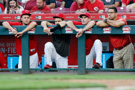 Cincinnati Reds starting pitcher Luis Castillo (58), third baseman Eugenio Suarez (7), hitting coach Turner Ward (31) and trainer Tomas Vera watch from the dugout in the second inning of the MLB National League game between the Cincinnati Reds and the Philadelphia Phillies at Great American Ball Park in downtown Cincinnati on Tuesday, Sept. 3, 2019. The game was tied 1-1 after three innings.