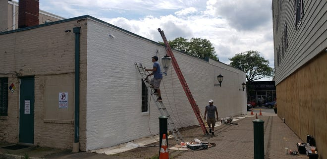 Blank wall being prepped for an outdoor mural in Somerville.