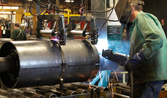 An employee of Pella-based Precision Inc. welds a product to be used for a conveyor belt. The company has factories in three other Iowa cities.