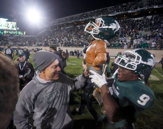 Isaiah Lewis hoists the Paul Bunyan Trophy with coach Mark Dantonio after MSU's 29-6 win over Michigan on Nov. 2, 2013.