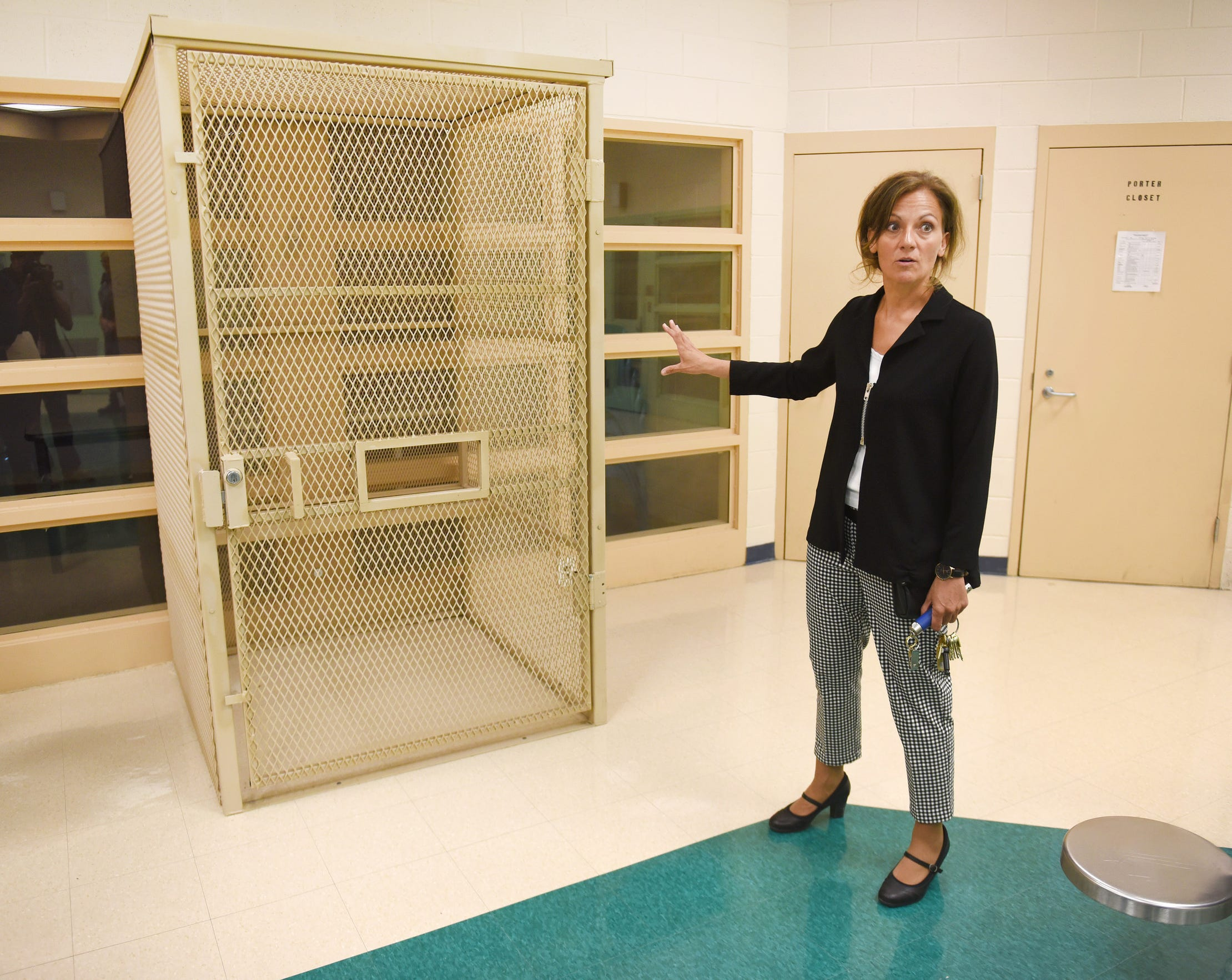 Warden Jodi DeAngelo shows a metal cage, or therapeutic module, that contains a bench for prisoners to sit on during therapy sessions.