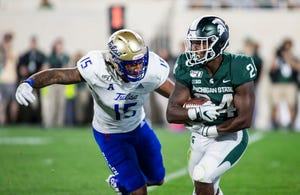Tulsa defensive end Trevis Gipson, left, attempts a tackle Michigan State running back Elijah Collins during the second half of the season opener in East Lansing.