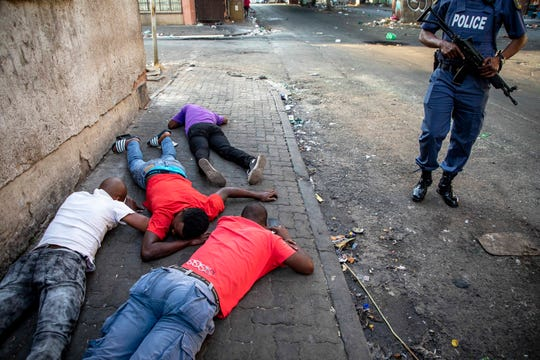 People lay on the ground after being arrested in Jeppe's Town, Johannesburg, Tuesday, Sept. 3, 2019. Police have struggled to stop looters who have been targeting businesses as unrest broke out in several spots in and around the city.