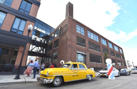 A 1951 Chrysler Windsor Deluxe Checker cab is parked in front of the Checker Cab Building, right, before the official opening Wednesday of the first phase of Elton Park.