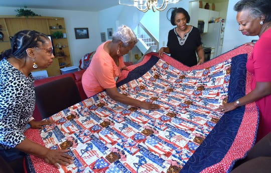 Great Lakes African American Quilters' Network officers, from left, Secretary Lorraine Hunter-Rooks of Detroit, Charity Quilt Chair Frances Jackson of Lathrup Village, President Wanda Nash of Livonia and Quilt Show Co-chair Karla Middlebrooks of West Bloomfield talk about this patriotic quilt that will be donated to a veteran's organization.