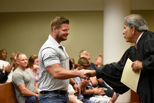 Judge Geno Salomone, right, gives a handshake and a certificate to Nicholas Simons after Simons completed the Regional DWI Court Program, Friday, July 12, 2019, at 23rd District Court in Taylor, Michigan.