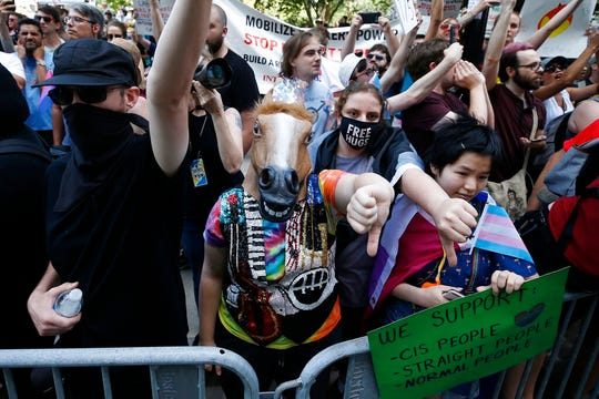 Counterprotesters, including one wearing a horse mask, line the route of the Straight Pride Parade in Boston, Saturday, Aug. 31, 2019.