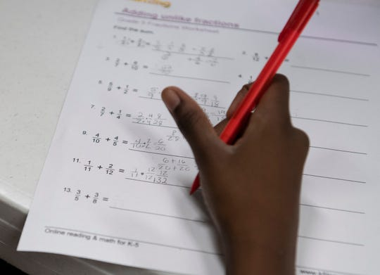 Tiana Jones, 11, works on adding fractions at Summit Church in Greenville during the GirlUp GVL program Tuesday, Sept 3, 2019.
