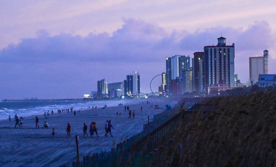 This file photo from Sept. 3, 2019, shows people walking and playing along the shoreline near evacuated hotels along North Ocean Boulevard in Myrtle Beach, South Carolina.