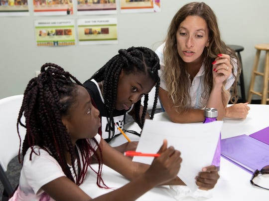 Kim Mogan (from right) goes over math work with Dashyia Wardlaw, 11, and Tiana Jones, 11, at Summit Church in Greenville during the GirlUp GVL program Tuesday, Sept 3, 2019.