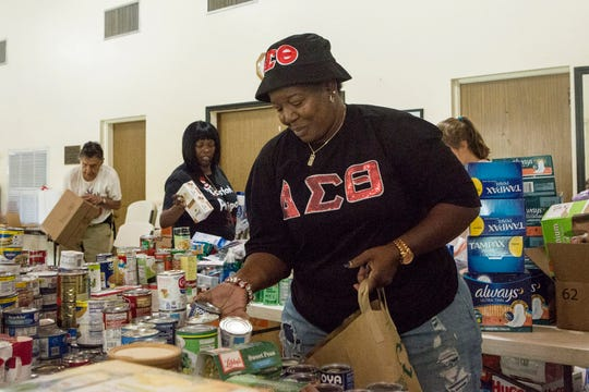 Volunteer Diane Alexander, 57, organizes donated goods slated to be sent to the Bahamas at Christ Episcopal Church in Miami, Tuesday, Sept. 3, 2019. Members of two historically black churches are sorting and preparing the supplies to be flown to the hurricane-ravaged islands of Abaco and Grand Bahama. (AP Photo/Ellis Rua)