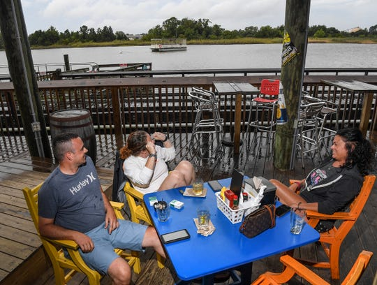Justin Patterson, left, Heather Richardson, and Beth Sabia, all of Georgetown, sit at Buzz's Roost, a restaurant and bar on Winyah Bay in Georgetown, South Carolina Wednesday, Septemeber 4, 2019. Locals come to the bar open through hurricane weather. Last year customers waded through water to get to the open restaurant with a bar.