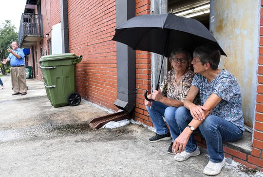 Lynette Cooper, left, and Julie Goude of Georgetown watch the rain starting as manager Tom Goode lays sandbags in front of Tomlinson's department store on Front Street in downtown Georgetown, South Carolina Wednesday, Septemeber 4, 2019. Built in 1904, the store is in the historic district and across the street from a the Fogel building where President George Washington stayed a night.