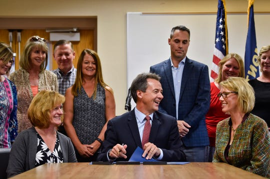 Gov. Steve Bullock, flanked by healthcare industry representatives, signs an executive order establishing Big Sky Care Connect as the state's designated Health Information Exchange Wednesday morning at St. Peter's Health in Helena, Mont. (Thom Bridge/Independent Record via AP)