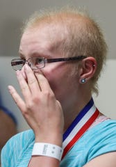 Jessie Lanzer wipes away tears before ringing the bell to celebrate.