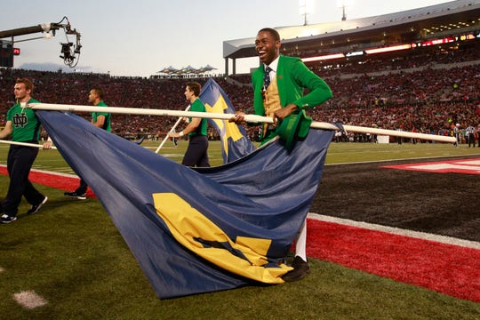 Notre Dame Fighting Irish leprechaun Samuel Jackson carries a Notre Dame flag in a game against the Louisville Cardinals during the first quarter at Cardinal Stadium.