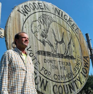 Jim Glasgow stopped to check out this sign he built in 2006 as part of a successful campaign to halt a proposed Johnson County road paving project. Now known as the World's Largest Wooden Nickel, it has become a tourist stop near I-80.