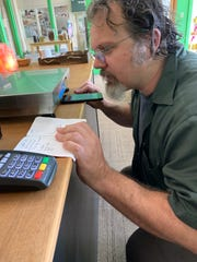 Patrick Jerome, general manager at Rainbow Co-op in Northpark, checks one of the scales.