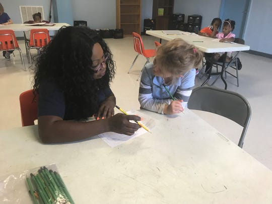 Sharmaine Kings works with a student on her homework at Boys and Girls Club of Humboldt.