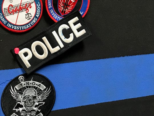 A collection of patches is pinned to a bulletin board that Jackson Police Department Intelligence Analyst Sarah Webb Jones hand-painted.