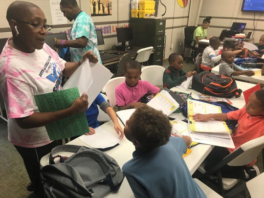 Gladys Robinson, director of Boys and Girls Club in Humboldt, hands out paper so some of the younger students can work on their spelling homework.