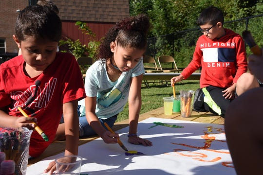 Silas Brack (left), Jayla Brack (center) and Adair Vargas enjoyed the Painting with a (Lemon) Twist activity after the dedication ceremony.