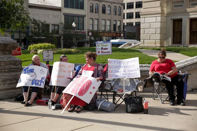 """From left, Sarah Melville, Elyse Romanovich, Kelly Jacobs and Melinda White, all teachers with the Lafayette School Corp, hold signs and grade during a """"grade-in"""" on the steps of the Tippecanoe County Courthouse, Wednesday, Sept. 4, 2019 in Lafayette."""