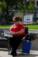 "Melinda White, a Spanish teacher at Lafayette Jeff, grades papers during a ""grade-in"" on the steps of the Tippecanoe County Courthouse, Wednesday, Sept. 4, 2019 in Lafayette."