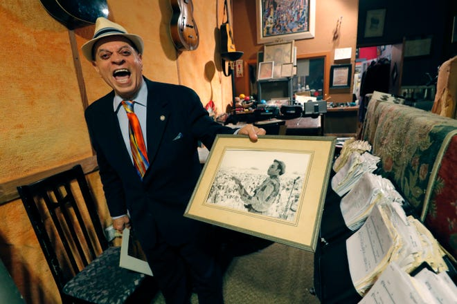 In this Wednesday, Aug. 28, 2019 photo Deacon John Moore shows a photo of himself performing approximately 50 years ago, as he talks about the 1969 New Orleans Pop Festival at his home in New Orleans. Fifty years ago, a couple weeks after the Woodstock music festival drew hundreds of thousands to farmland in New York, there was a smaller, bayou-country re-enactment of sorts. It was called the New Orleans Pop Festival, although it took place 60 miles away, it featured several of the same acts as Woodstock. Also on hand was Deacon John, who at 78 is still a renowned New Orleans performer.