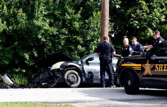 Lancaster Police officers investigate a head-on collision between a Fairfield County Sheriff's Office cruiser and a car deputies were pursuing Wednesday morning, Sept. 4, 2019, on Duffy Road in Lancaster. One deputy and two people in the car were taken to Fairfield Medical Center for treatment.