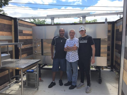 Chef Chad Humes (left), restaurateur Peter Ginopolis and his son Nicholas Ginopolis show off a large smoker installed on the patio of their new barbecue restaurant Ginopolis' Bar-BQ & Speakeasy in downtown Brighton, Wednesday, Sept. 4, 2019.
