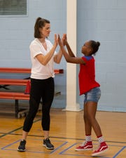 Louisville Ballet's outreach coordinator Molly Kays dances with students at Portland Community Center.
