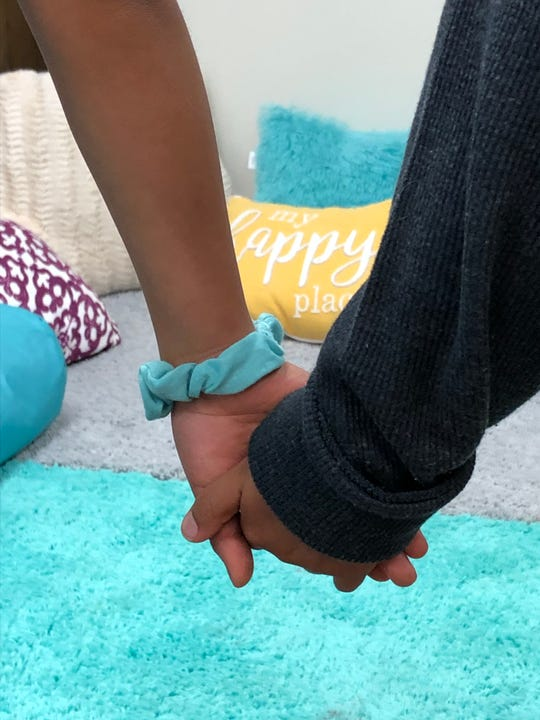 Two refugee children clasp hands at an East Lansing program for children in transitional foster homes in an undated photo. Bethany Christian Services and Samaritas are seeking new foster homes to help children.