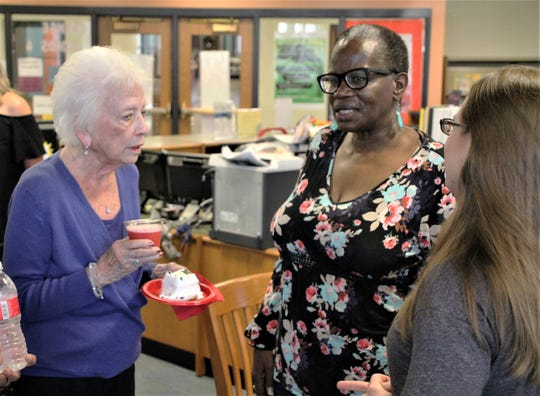 Mary Ellen Withrow, left, talks with former Marion City Schools teacher Tara Dyer, center, and other guests during a reception on Tuesday at Grant Middle School.