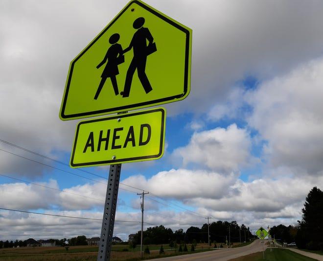 A sign along North Shore Drive in Hartland alerts motorists that a school crossing is ahead.