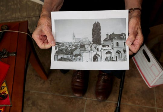 Eugene Schulz holds a photo of the city of Chartres in 1944 he took two days after its liberation.