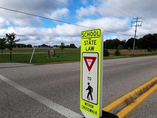 A sign near North Shore Middle School in Hartland tells motorists they must yield to pedestrians in the crosswalk.