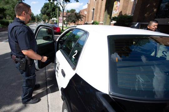 Community liaison officers for the Milwaukee Police Department Jose Acevedo, left, and Eliel Contreras get into their police cruiser.