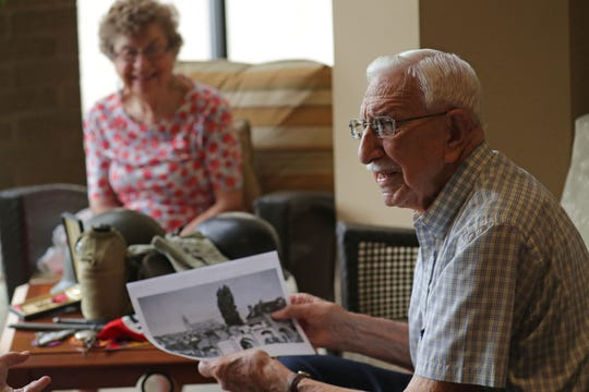 Eugene Schulz holds a photo of the city of  Chartres in 1944 he took two days after its liberation. His wife Eleanore is seated in the background at Harwood Place Retirement Community in Wauwatosa.