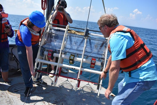 Members of the Adler Planetarium's Aquarius Project drop an underwater sled with powerful magnets into Lake Michigan near Manitowoc to look for pieces of a meteorite that dropped into the lake in 2017.