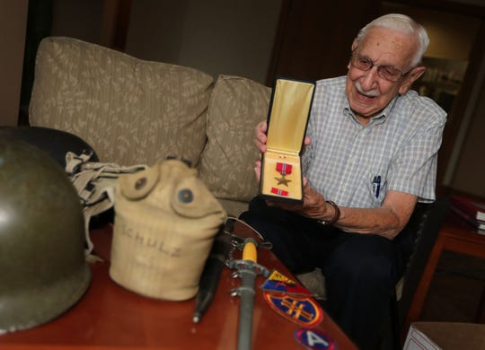 World War II veteran Eugene Schulz displays his Bronze Star along with other items he collected during his time in the service, at Harwood Place Retirement Community in Wauwatosa. Schulz helped liberate Chartres, France, and he has been invited back to the city to help celebrate the 75th anniversary of the city's liberation from the Nazis.
