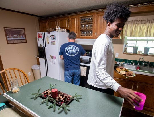 Prattville football player Isaiah Causey, right, prepares to  eat dinner at his home in Prattville, Ala., on Monday September 2, 2019.
