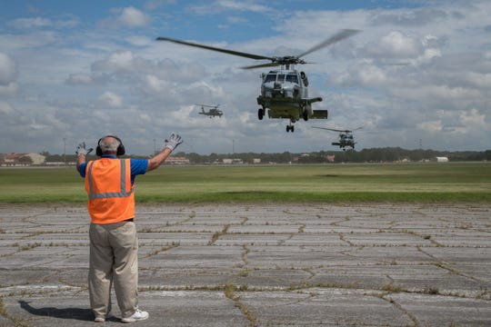 An Airman from the 42nd Operational Support Squadron directs U.S. Navy MH-60R Sea Hawk helicopters as they arrive at Maxwell Air Force Base, Alabama, from Naval Air Station Jacksonville and Naval Station Mayport, Florida, Sept. 1, 2019. The helicopters evacuated from the Jacksonville area in advance of Hurricane Dorian. In addition to the helicopters, Maxwell AFB is serving as an Incident Support Base for Federal Emergency Management Agency and Defense Logistics Agency personnel and equipment.