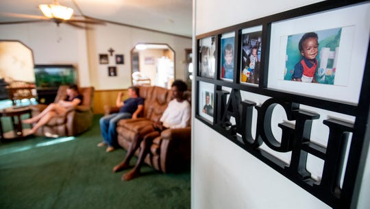 A photo of Prattville football player Isaiah Causey when he was young hangs on the wall, right, as he and his parents Marsha and Terry Causey watch television at their home in Prattville, Ala., on Monday September 2, 2019.