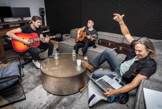 Simon Dumas, left, and Caleb Miller, center, of the band King Calaway work in a writing room with songwriter James T. Slater at BMG's new office building Sept. 4, 2019.