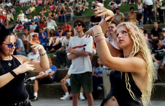 Alicia Wing, left, and Sophia Axley, right, of White House, Tennessee, dance to the music of Jetpack during a Dancin' in the District concert at Riverfront Park on July 25, 2002.